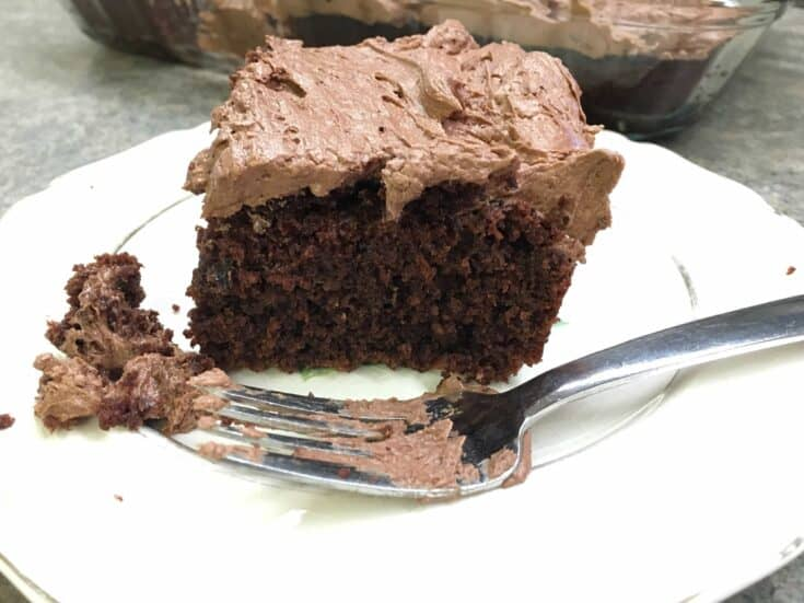 Chocolate cake with buttercream frosting on a plate with a fork