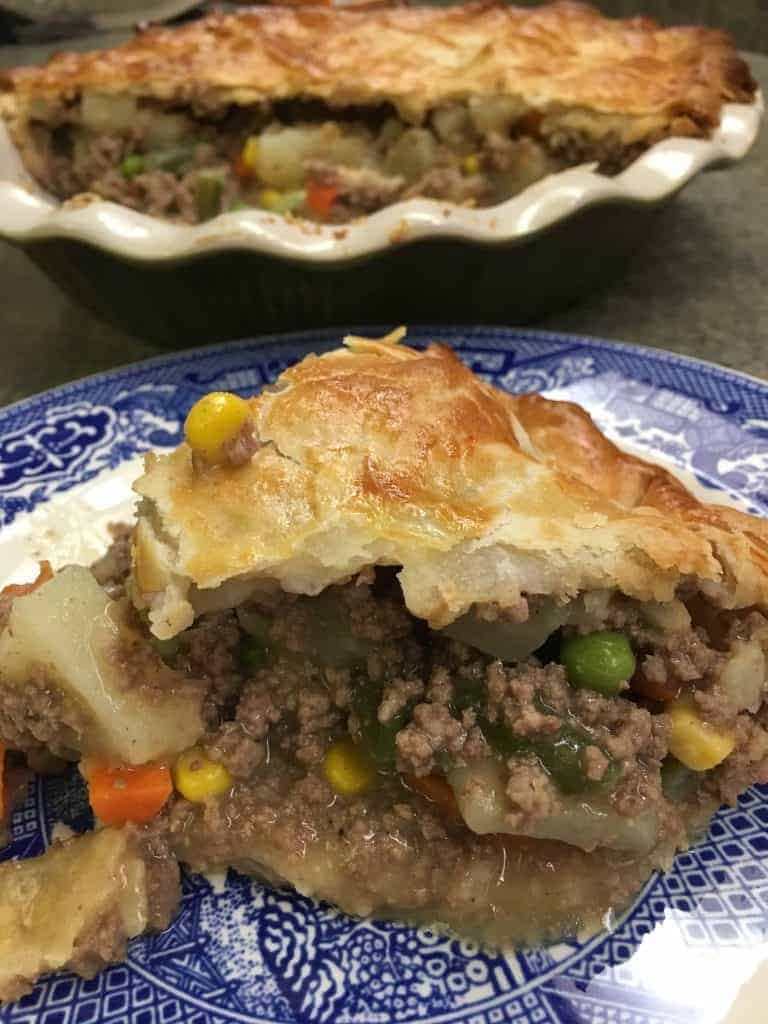 Easy ground beef pot pie cooked and sliced on a blue and white plate.