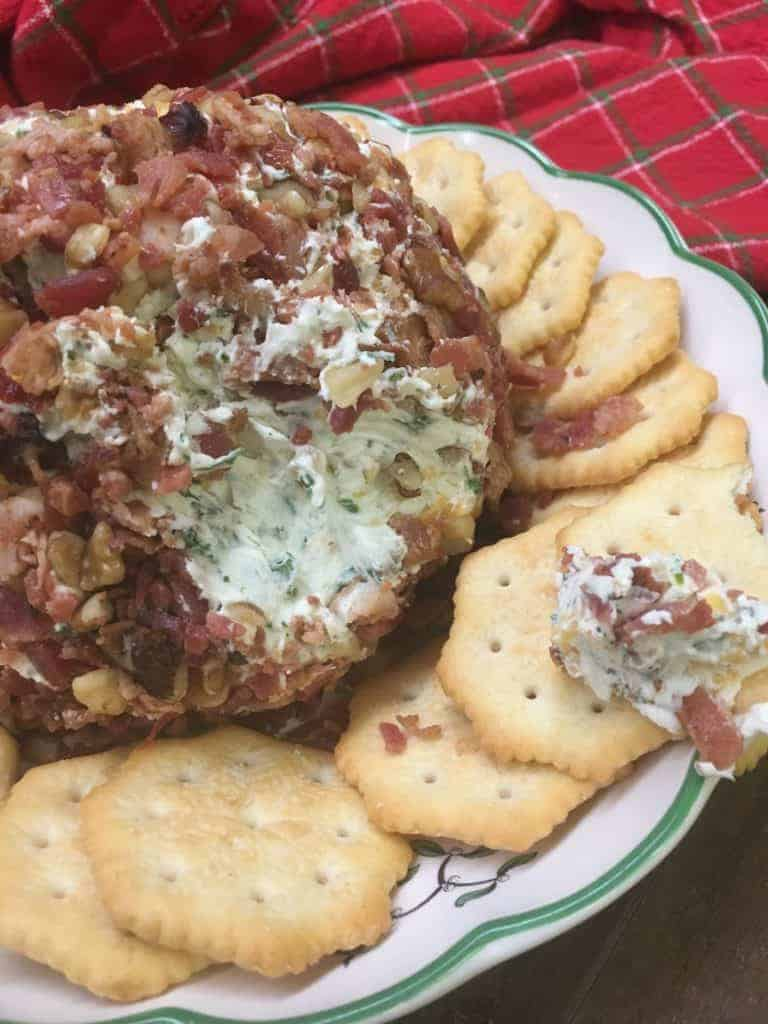 A cheese ball with crackers on a plate.