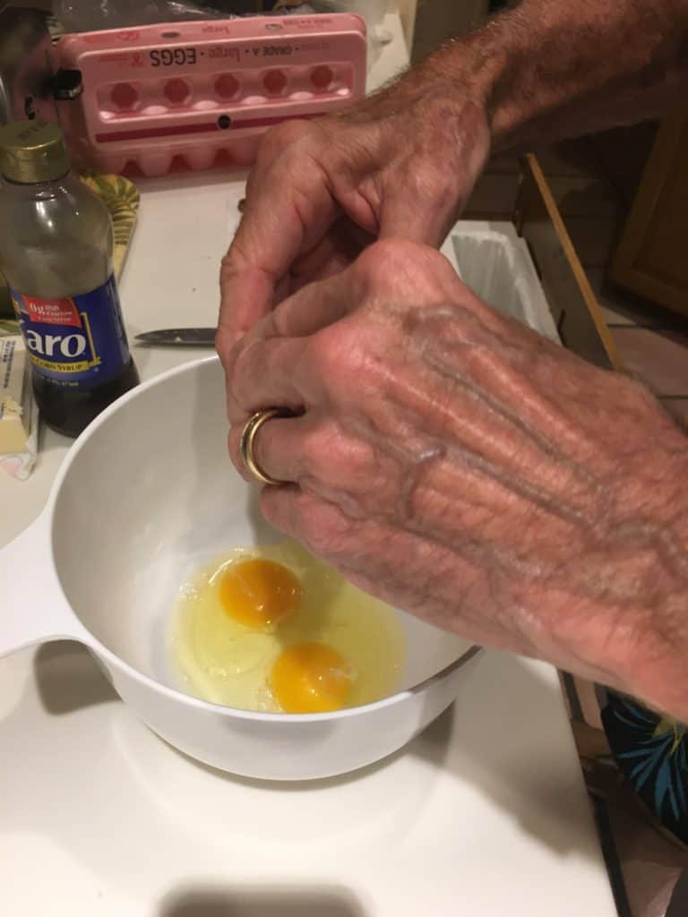 Breaking eggs into a bowl for pecan pie