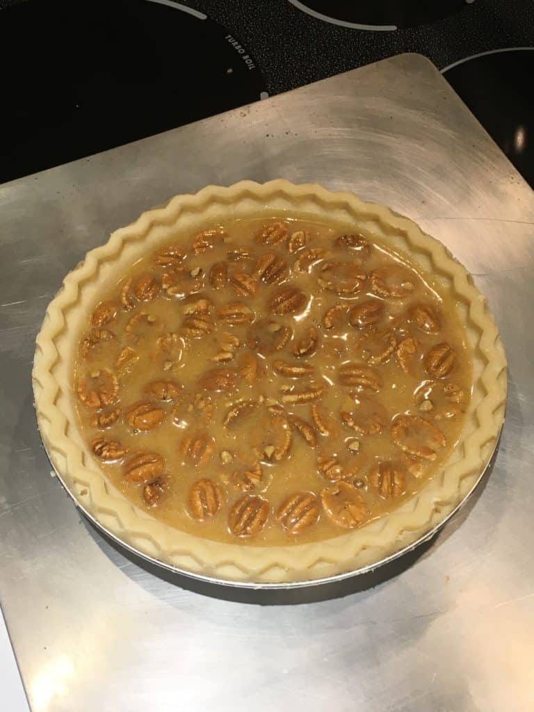 Uncooked pecan pie sitting on a cookie sheet.