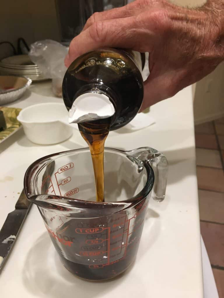 Pouring corn syrup into a glass measuring cup for pecan pie