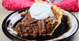 Pecan pie on a plate with a dollop of whipped cream