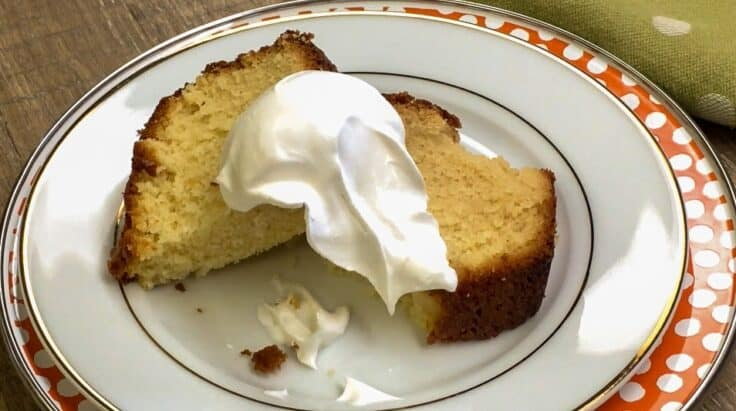 Pound cake on a plate with whipped cream on top