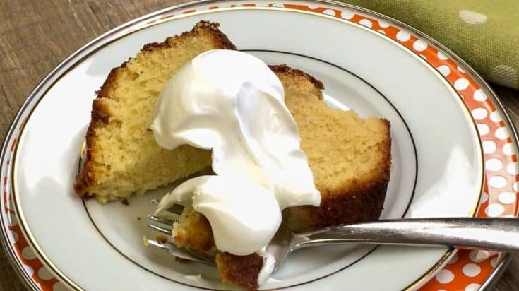 Pound cake with whipped cream on a plate with a fork