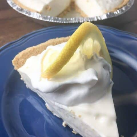 A slice of lemon pie on a blue plate with a lemon on top.