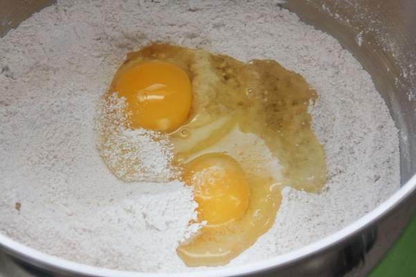 Two eggs in a bowl with flour, sugar, and cinnamon.