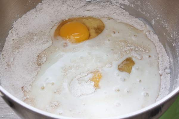 Buttermilk, vanilla extract, eggs, flour, and sugar in a metal mixing bowl.