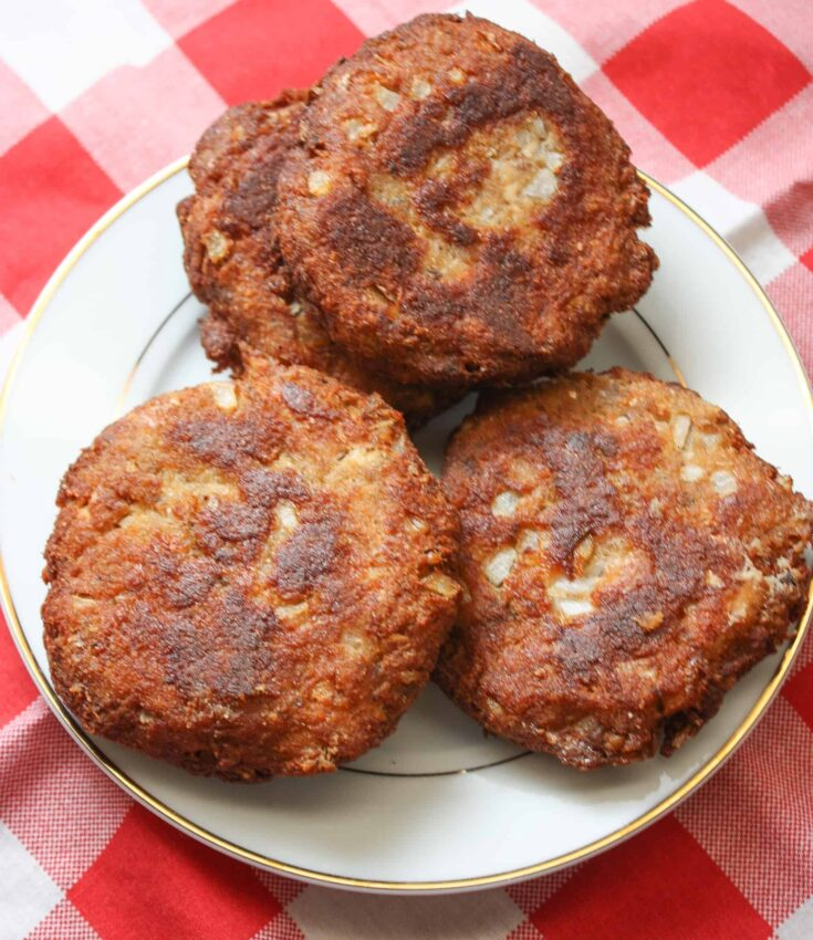 Salmon patties on a white plate with a checked red and white tablecloth