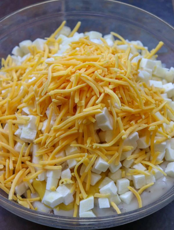 Picture of shredded cheddar cheese on top of a bowl of potatoes.