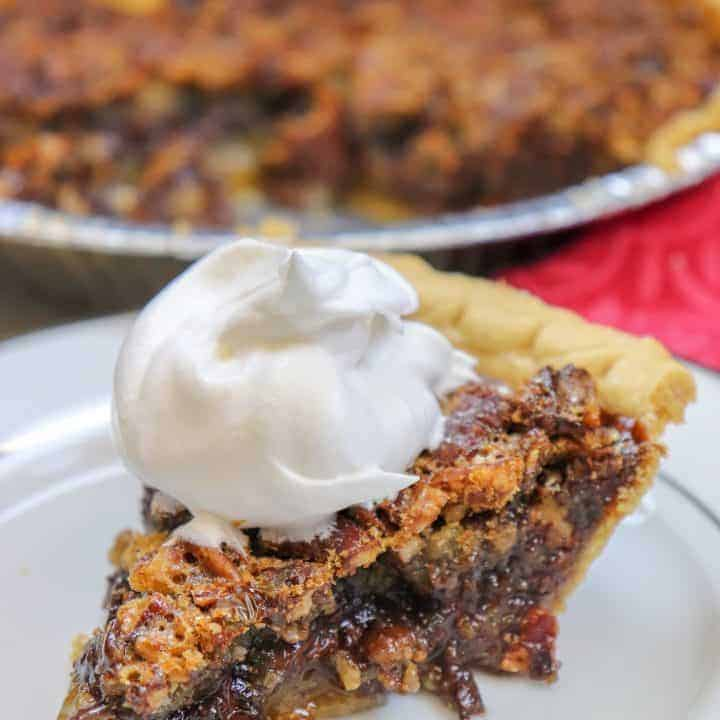 Picture of pecan pie with whipped cream on top.