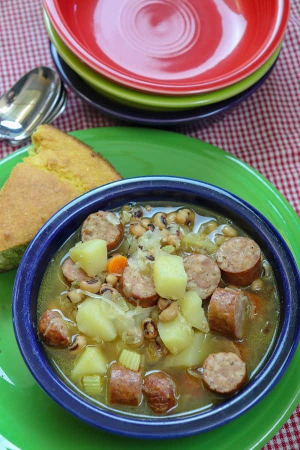 Picture of veggie soup in a bowl with smoked sausage.
