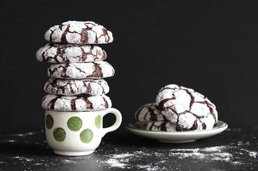 Chocolate cookies sitting on a plate and a teacup