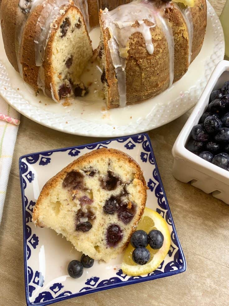 Lemon blueberry cake on a plate with lemons and blueberries