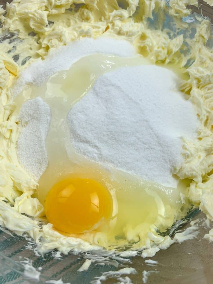Butter, sugar, cream cheese, and an egg in a bowl