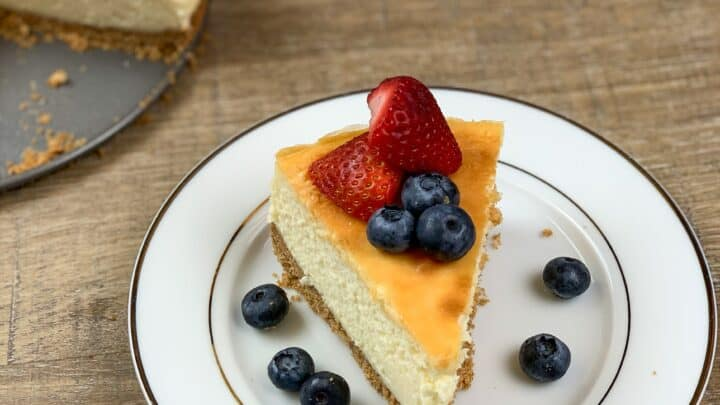 Cheesecake on a plate with strawberries and blueberries