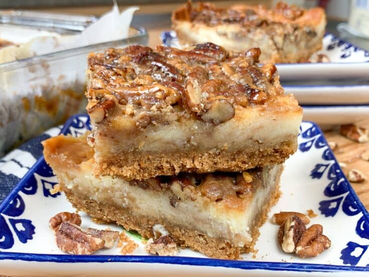 Pecan pie cheesecake bars stacked on a plate together