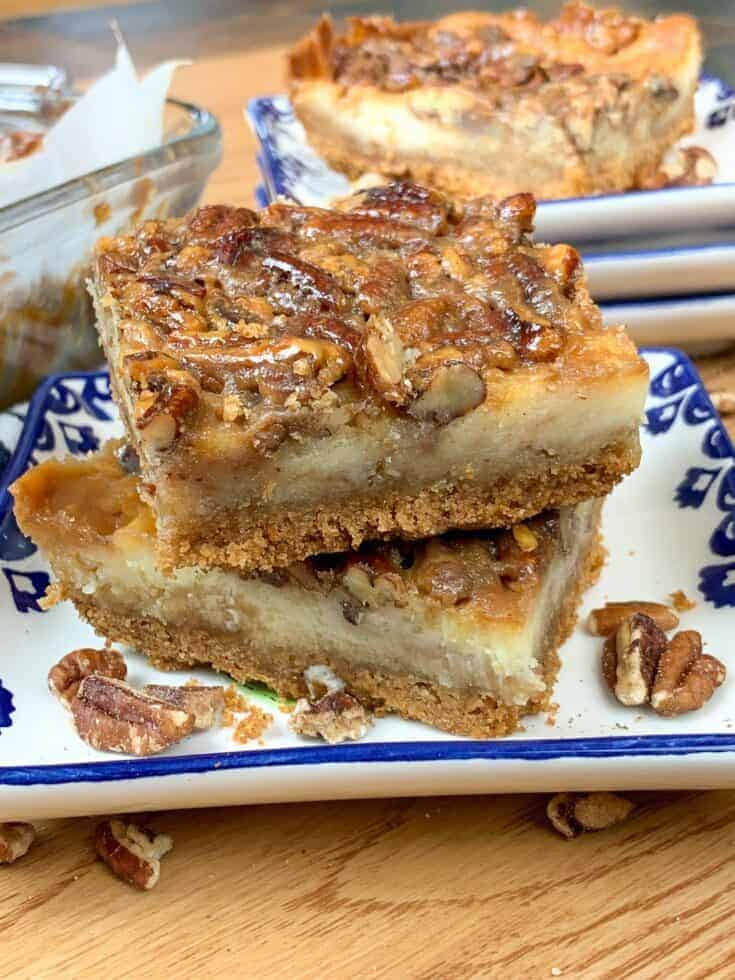 Pecan pie cheesecake bars stacked on a plate