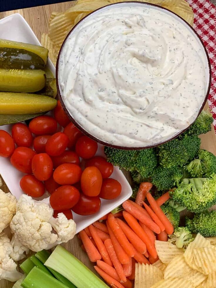 Sour cream and onion dip in a bowl surrounded by veggies