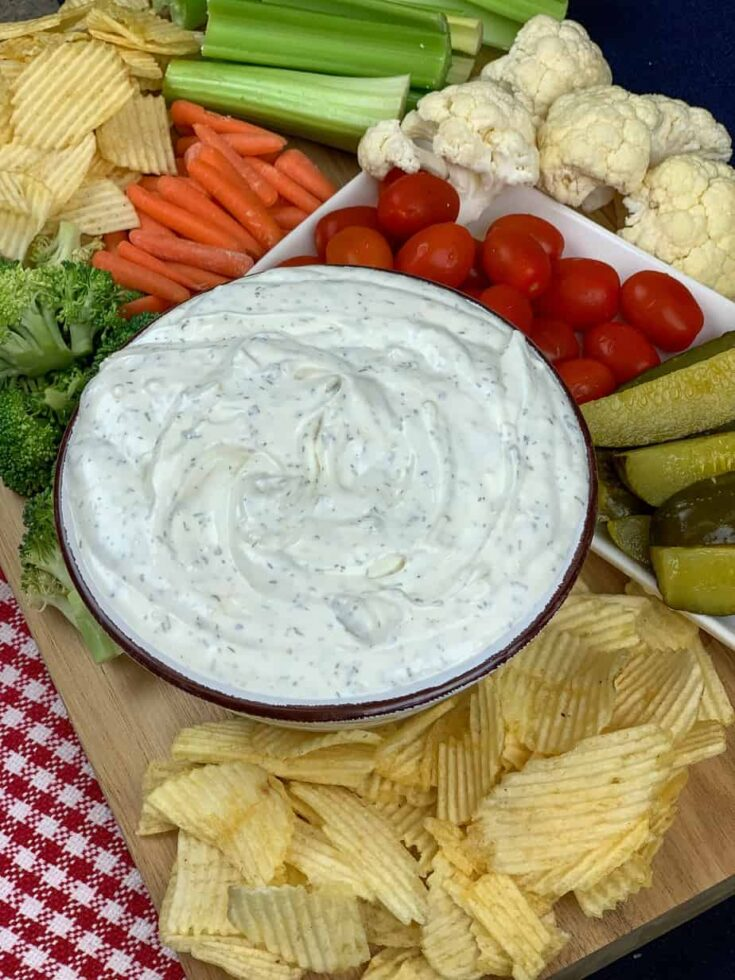 Sour cream dip in a bowl with veggies and chips on a board.