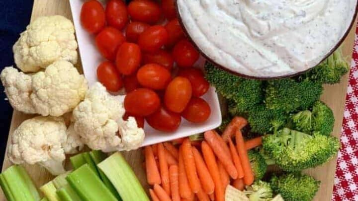 Sour cream dip and veggies on a cutting board