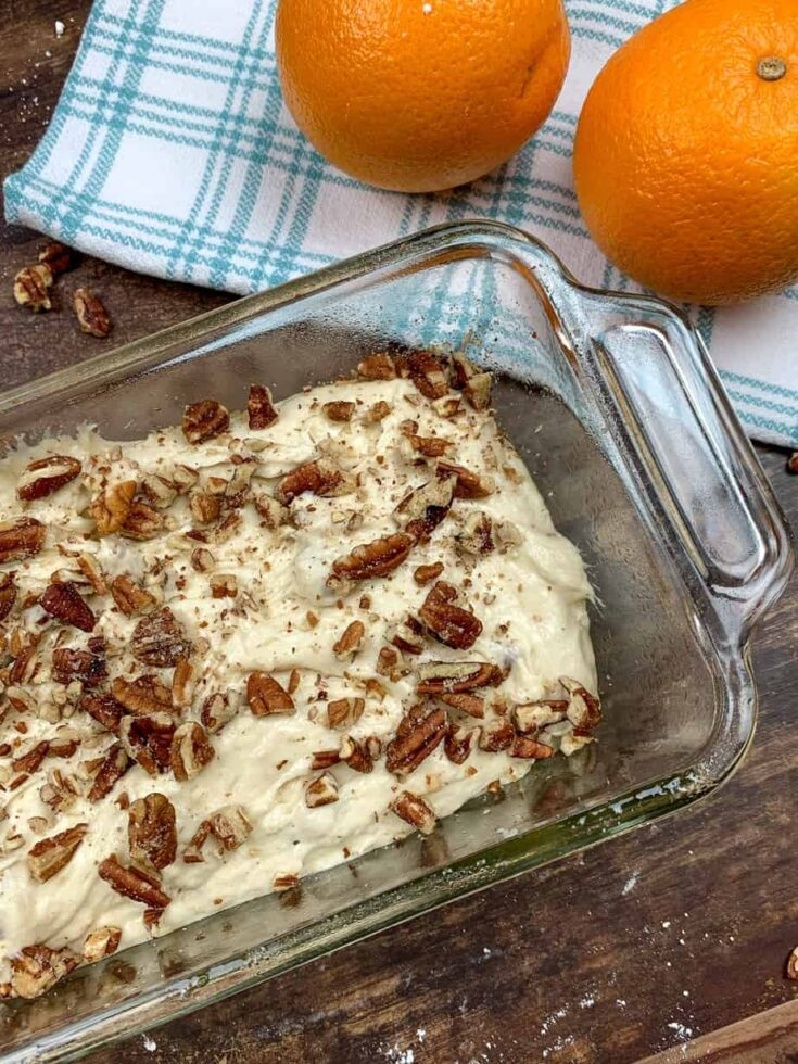 Banana bread mixture with pecans in a bread dish.