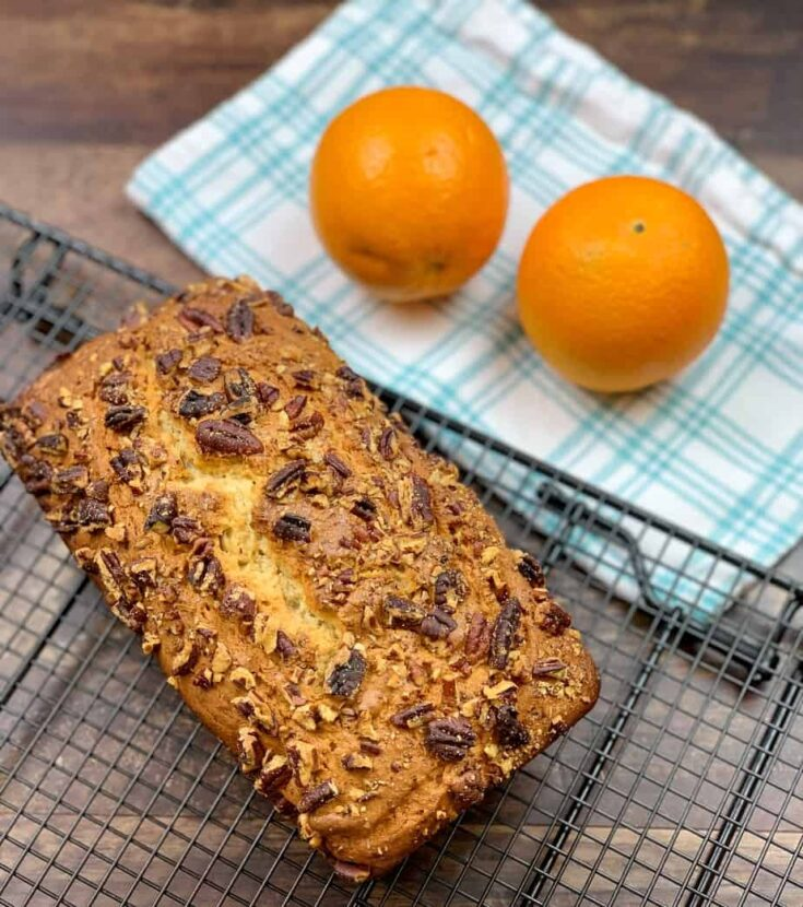 Baked banana bread on a cooling rack with oranges.