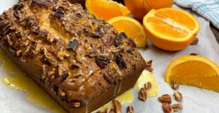 Banana nut bread with oranges on a counter
