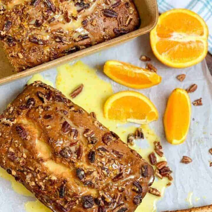 Two loaves of banana nut bread on a counter with orange slices