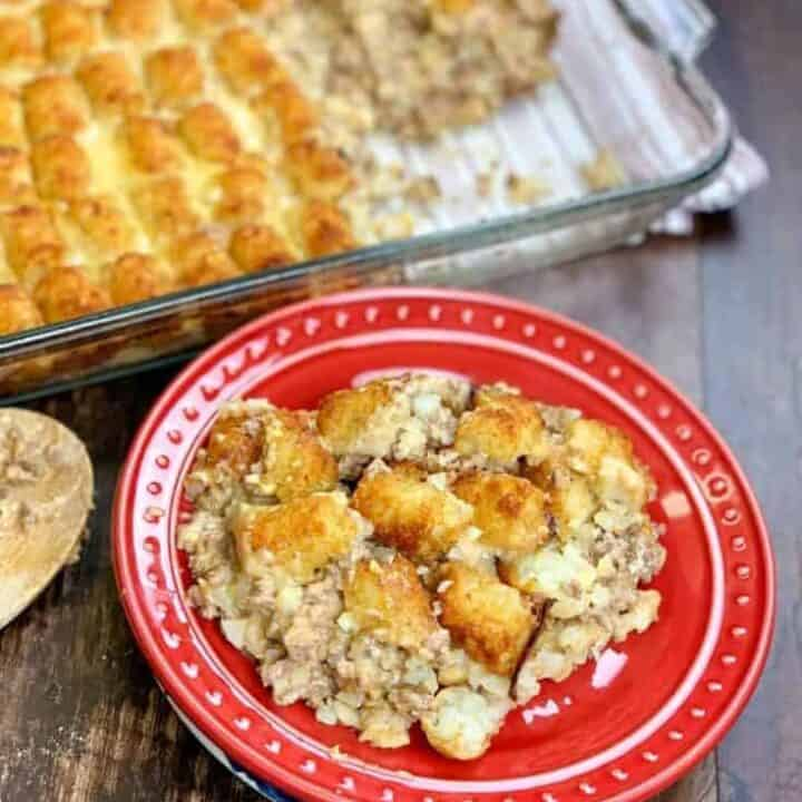 Tater tot casserole on a red plate next to a casserole dish