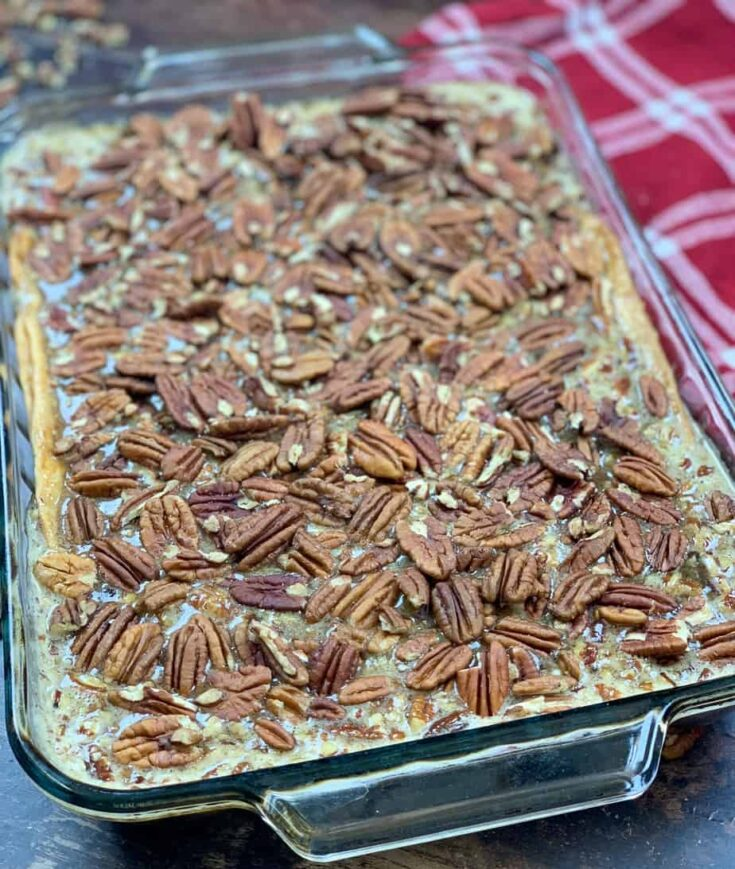 Pecan pie cobbler in a casserole dish with a red towel on the side