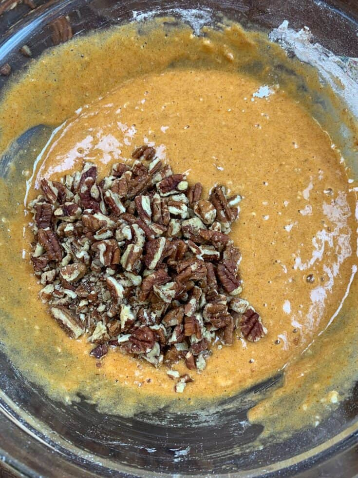 Pumpkin roll ingredients and pecans in a glass bowl