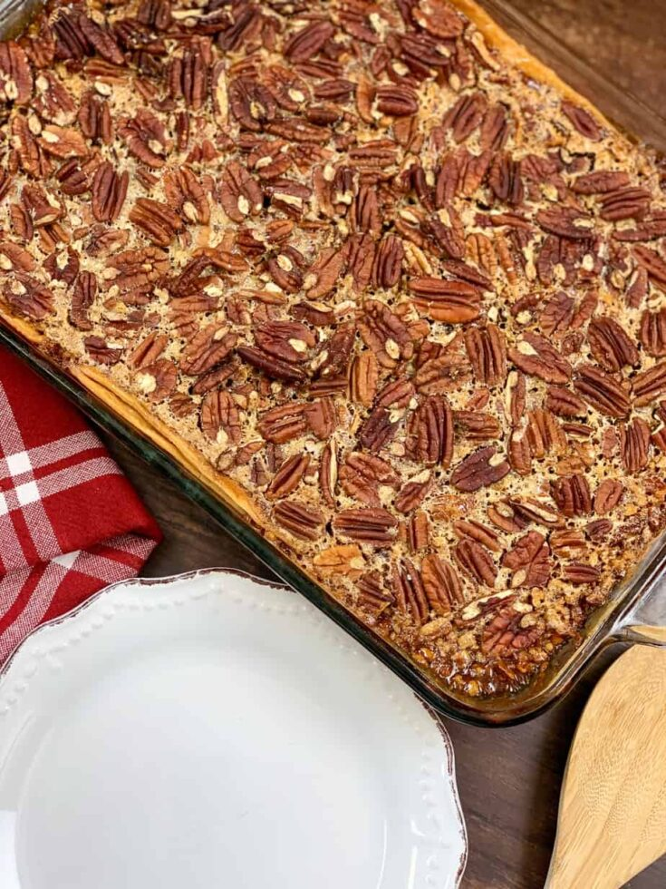 Pecan pie cobbler in a casserole dish and a white plate