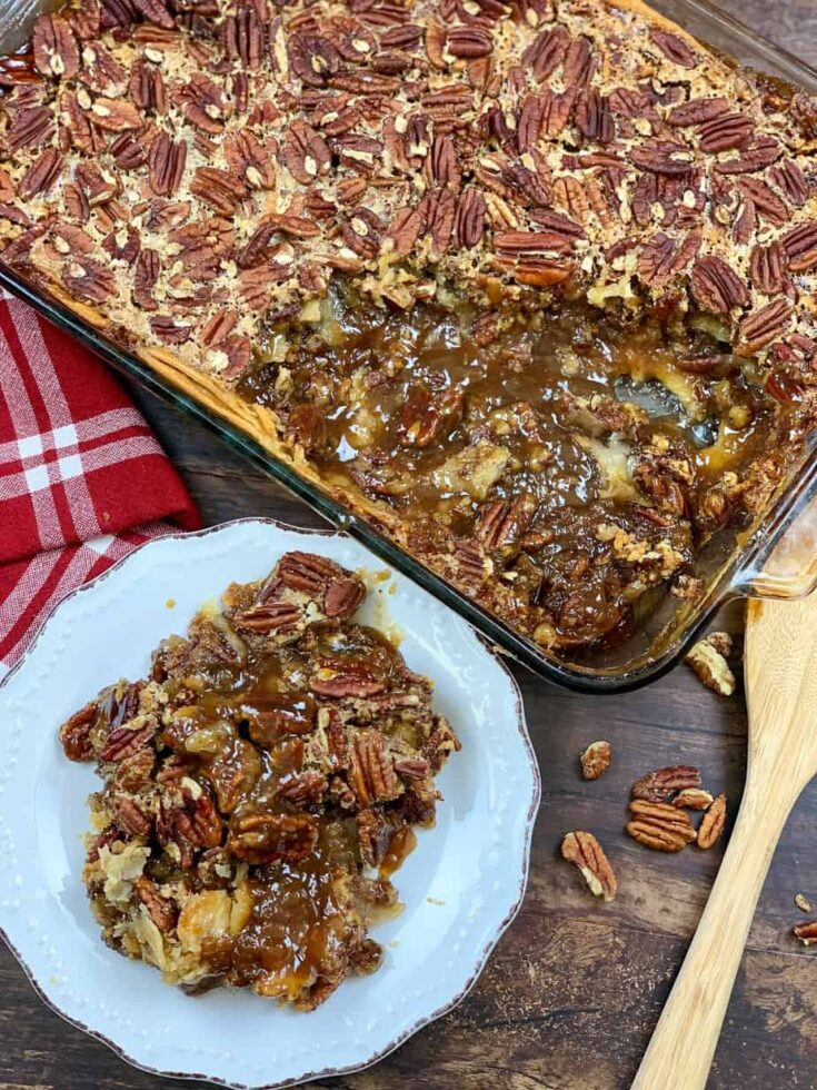 Pecan pie cobbler on a plate with a wooden spoon and casserole dish