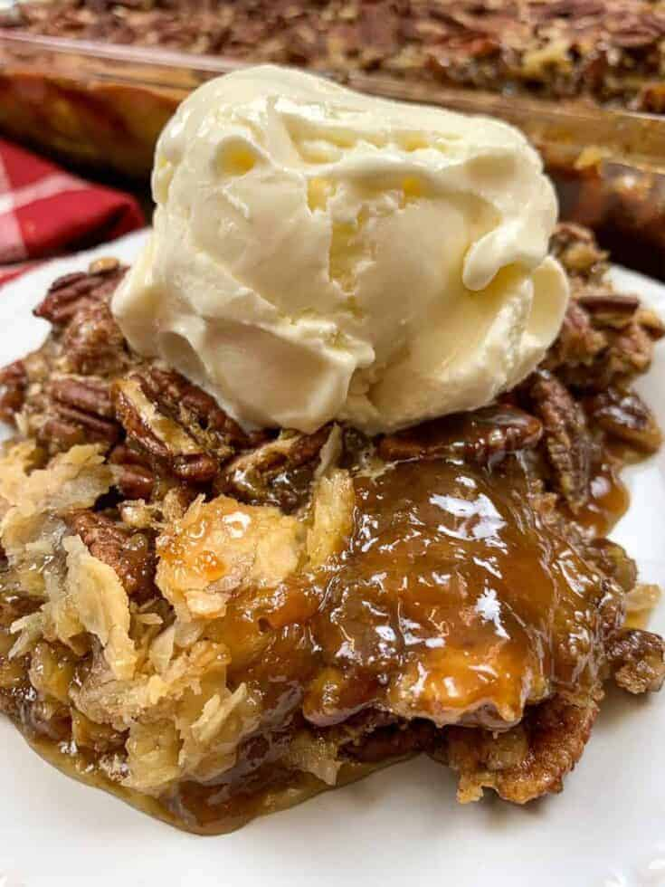 Pecan pie cobbler on a white plate with a scoop of ice cream