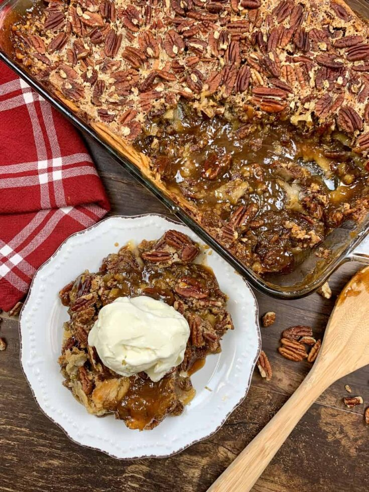 Pecan pie cobbler with ice cream on a plate and in a casserole dish.