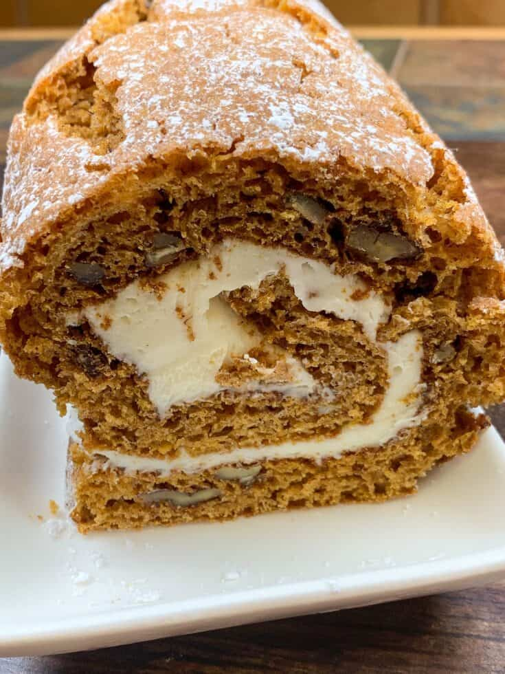 Sliced pumpkin roll with cream cheese frosting on a plate