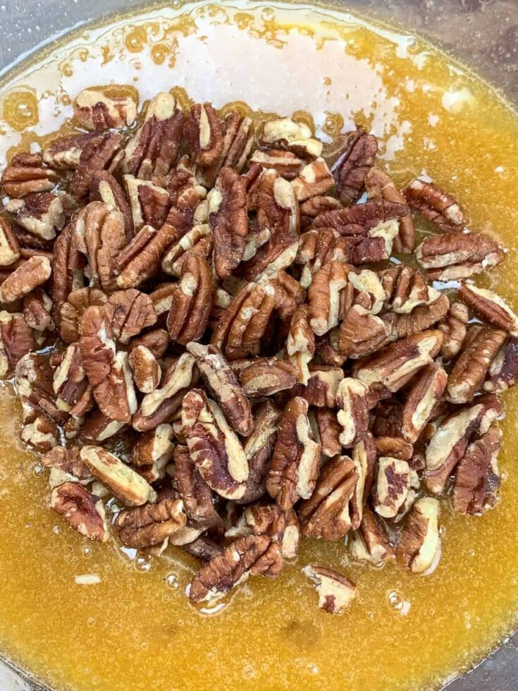 Pecans in a bowl with pecan pie filling