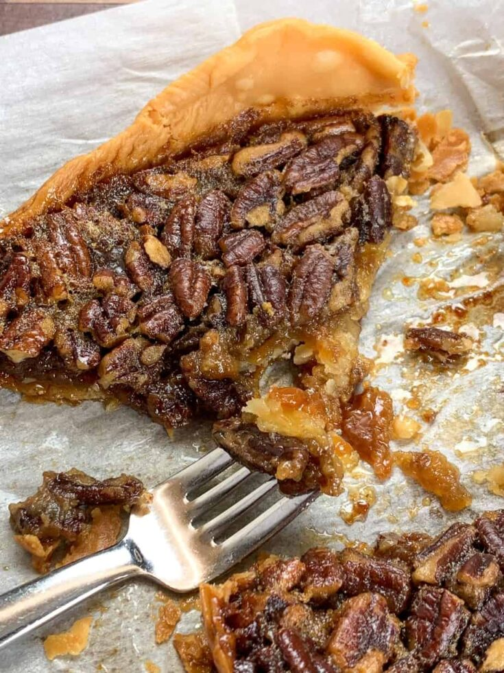A slice of pecan pie on a piece of parchment paper.
