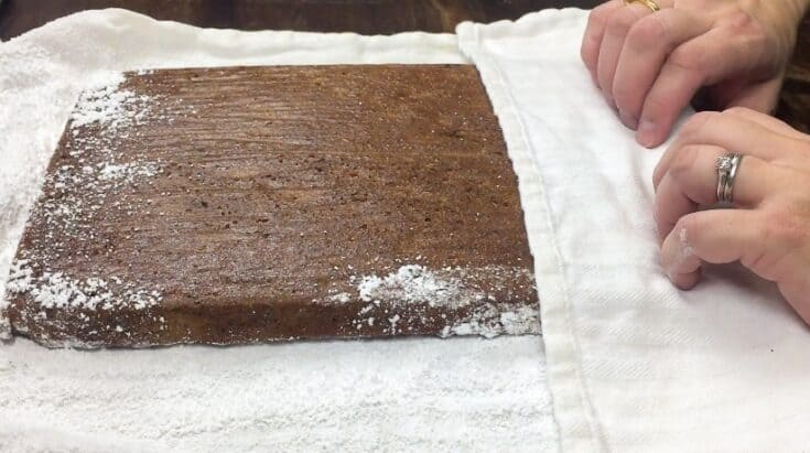 Rolling up the pumpkin roll on a towel covered with powdered sugar