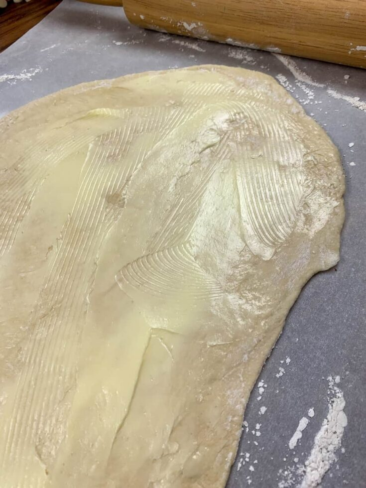 Pizza dough rolled out onto parchment paper with butter spread on top