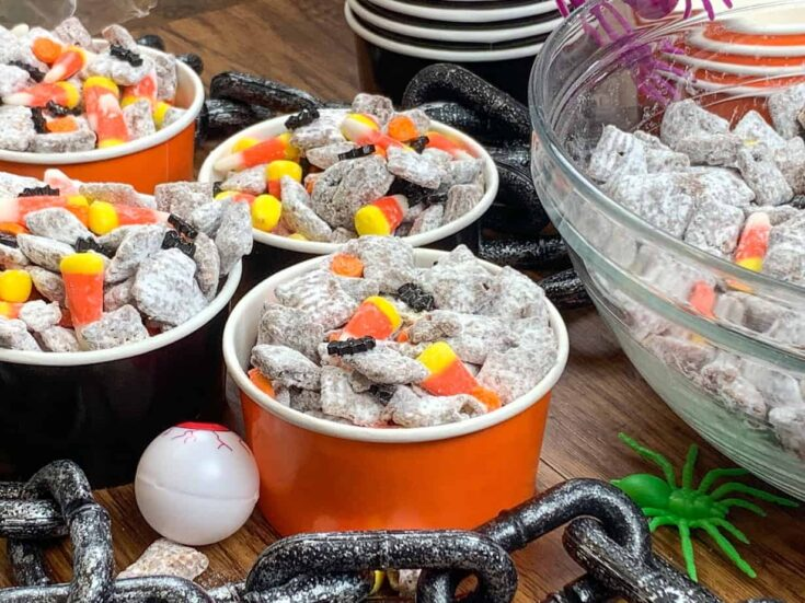 Halloween Muddy Buddies in containers on the counter with Halloween decorations