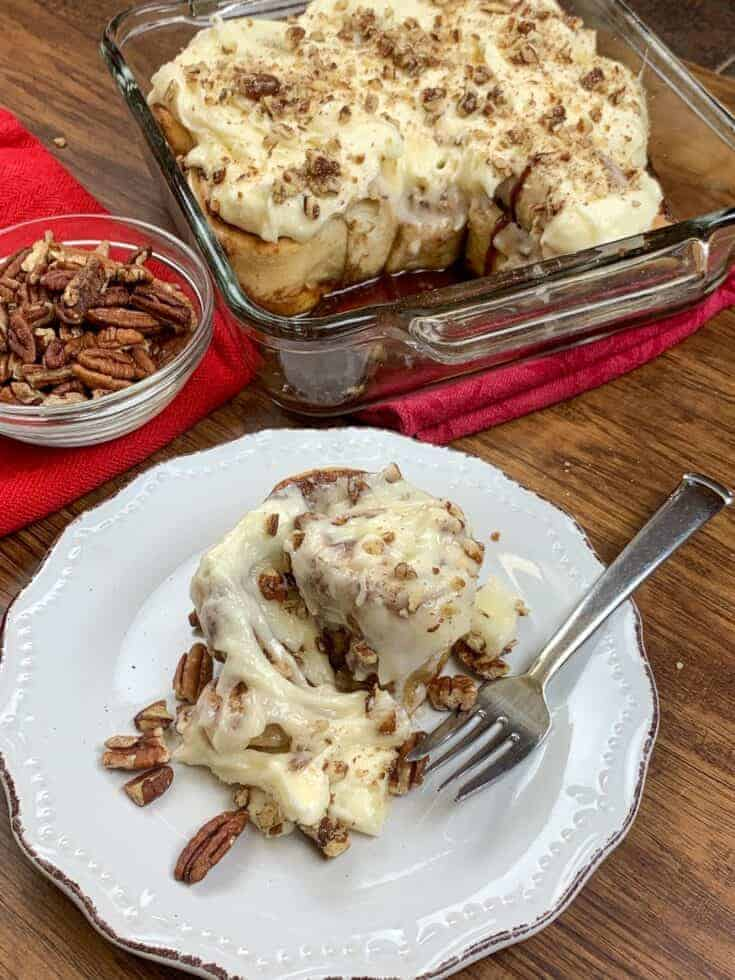 Cinnamon rolls in a dish and on a plate with pecans