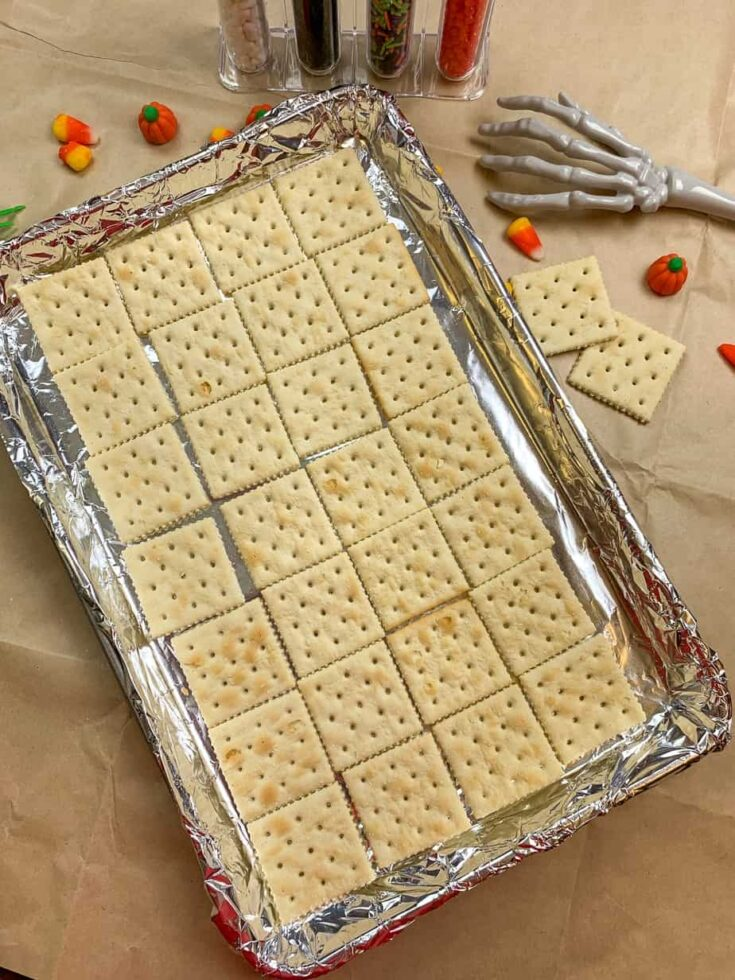 Saltine crackers laid out on a cookie sheet for crack candy