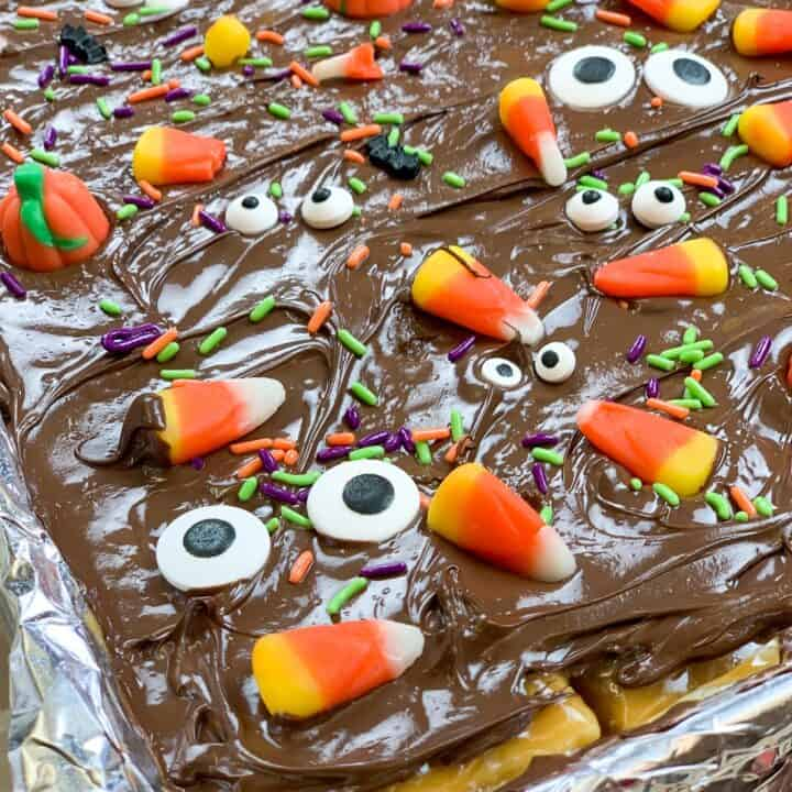 Halloween candy sprinkled on top of chocolate, toffee, and crackers