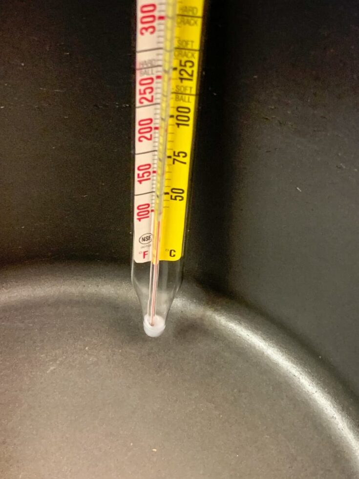 A thermometer on the side of a saucepan.