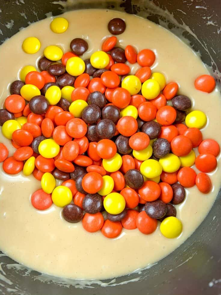 Reese's pieces in a saucepan with melting peanut butter fudge