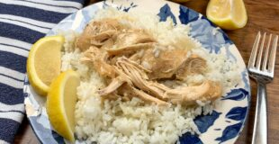 Lemon chicken and rice on a plate with lemons