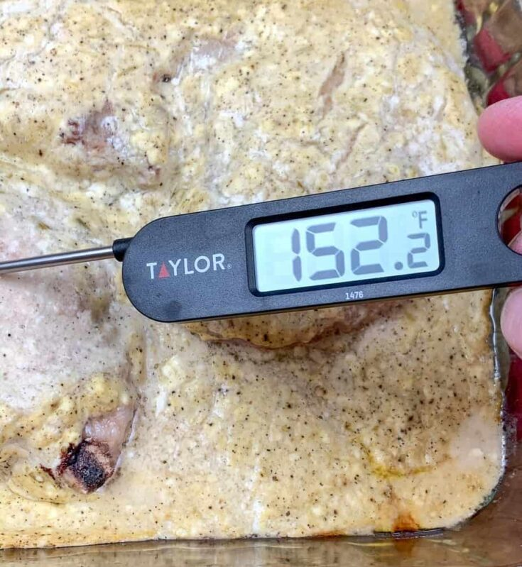 A digital thermometer resting inside of cooked pork chops with gravy