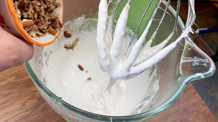Pouring pecans into divinity fudge mixture